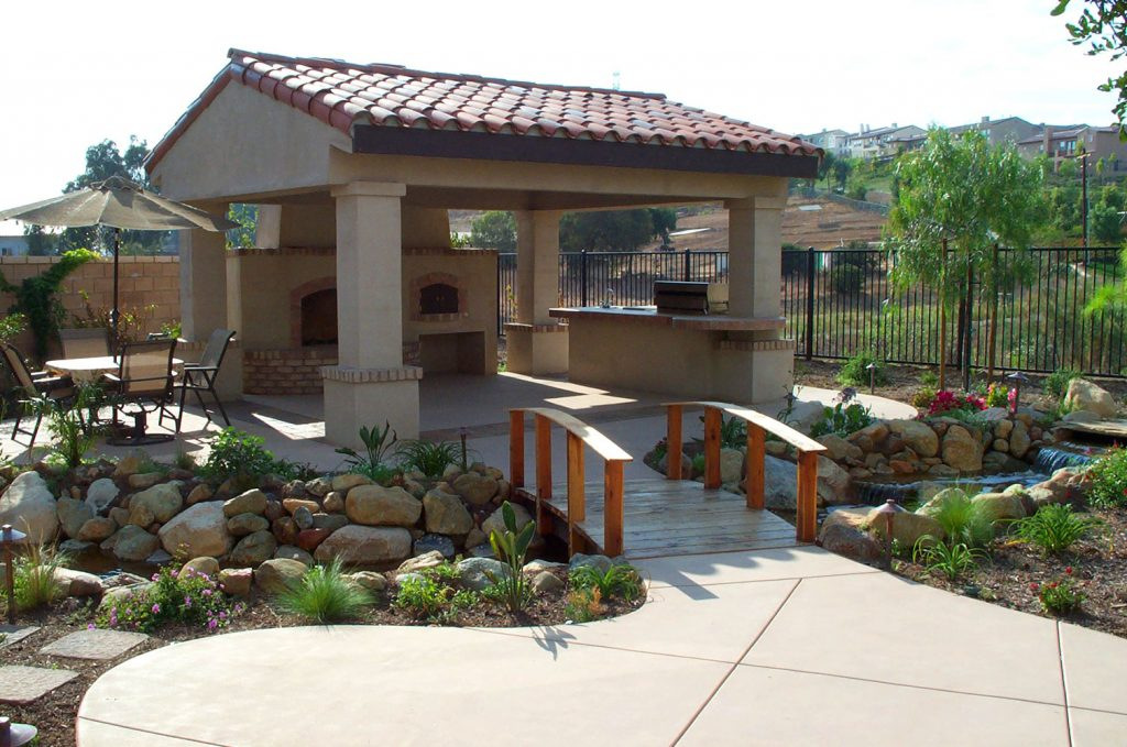Patio cover over fireplace, kitchen, stream with bridge construction