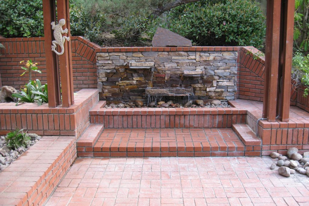 Rock wall waterfall and brick patio construction and design