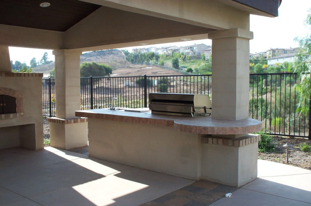 Covered outdoor entertaining space with kitchen island construction