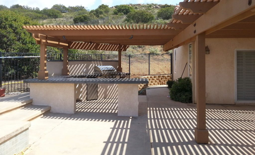 Large pergola over outdoor kitchen island and bar