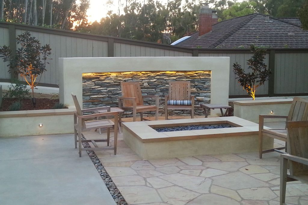 Modern outdoor fire table and rock waterfall design and construction