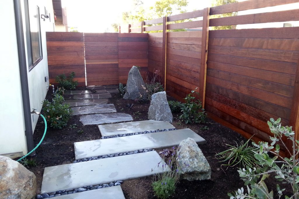 Modern horizontal fence construction with side yard walkway and landscaping