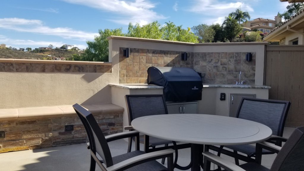 outdoor kitchen island construction with built-in seating