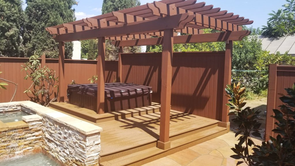 Pergola over wooden deck around hot tub construction