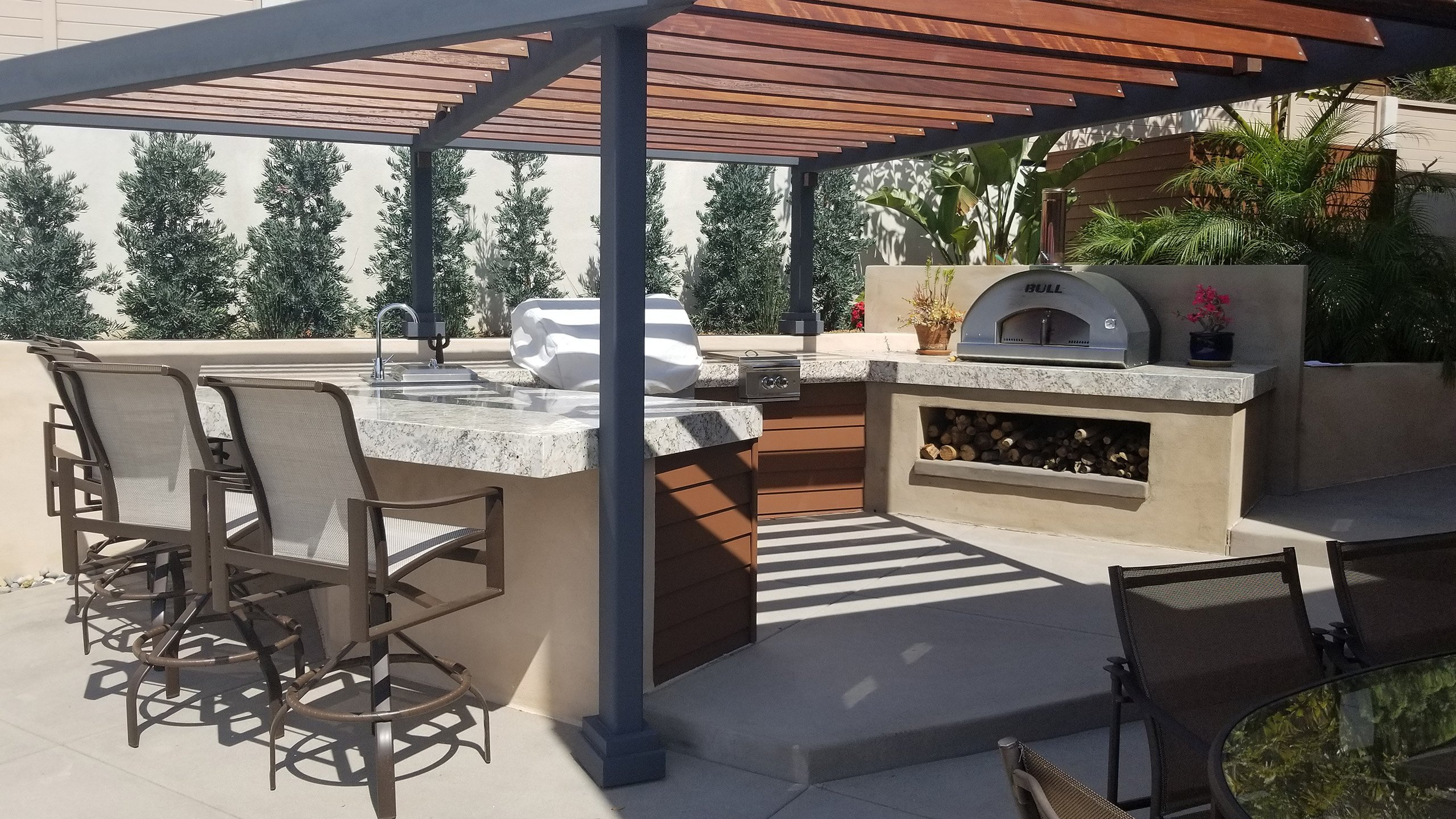 Outdoor kitchen construction with pizza oven and bar