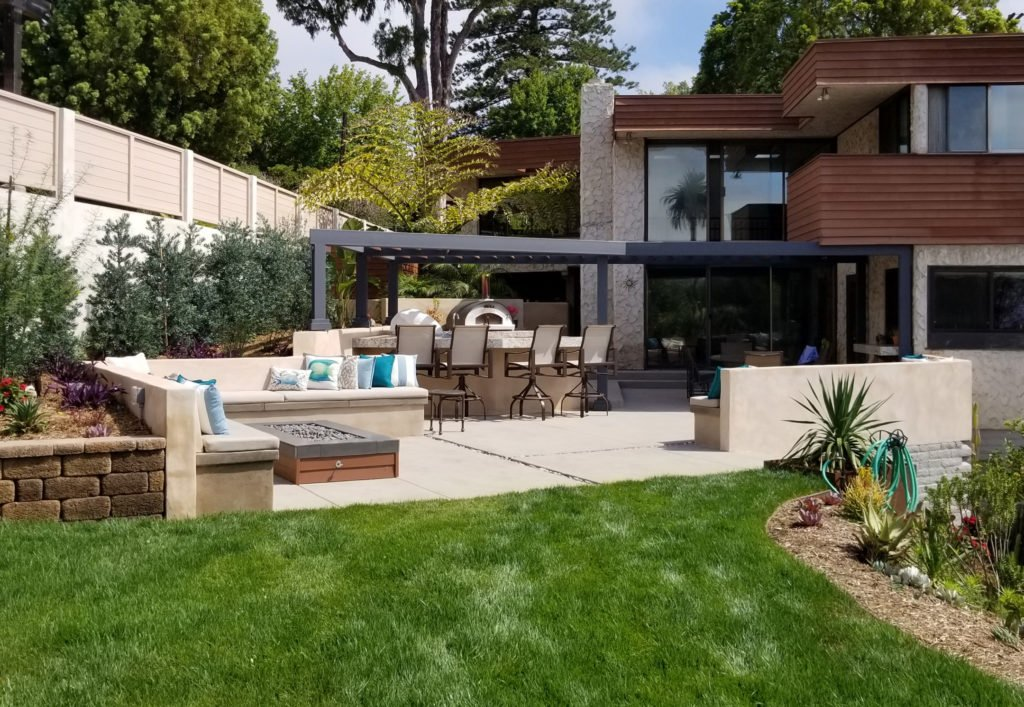 Modern back yard design with kitchen, fire table and concrete seating