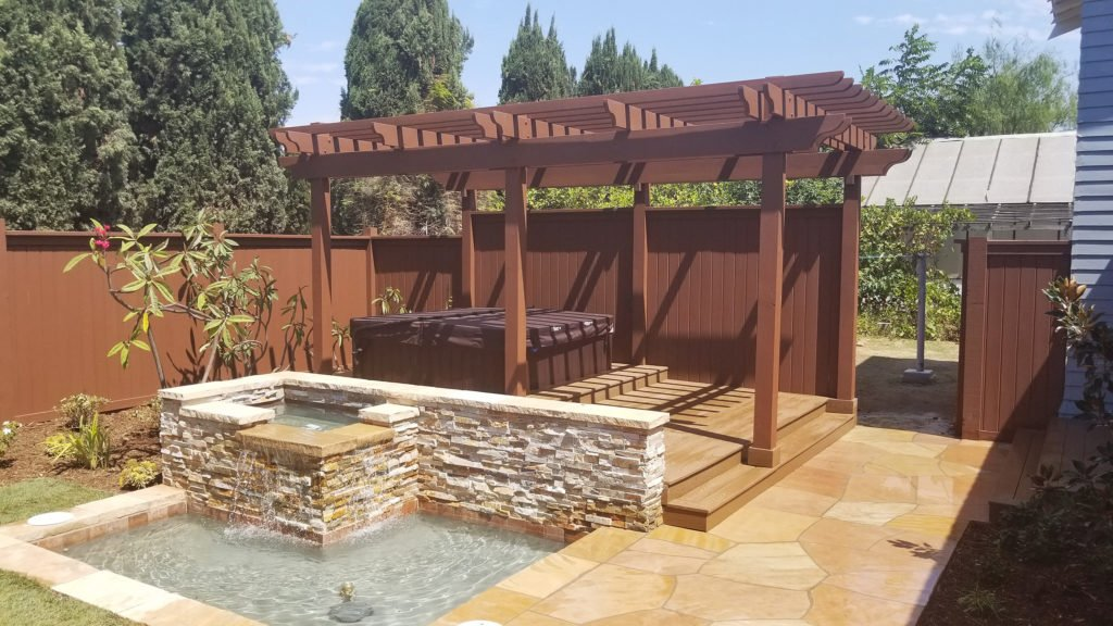 Relaxing back yard design with wood pergola over built in hot tub