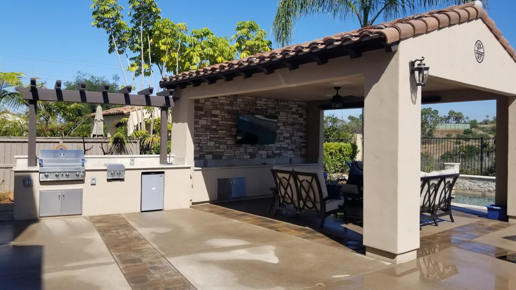Outdoor kitchen with Spanish style patio cover entertainment area